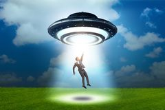 The flying saucer abducting young businessman stock photography