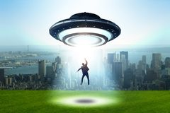 The flying saucer abducting young businessman royalty free stock image