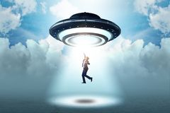 The flying saucer abducting young businessman royalty free stock photography