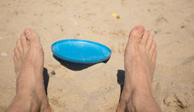 Flying saucer. Lying on the sand between his legs Royalty Free Stock Photography