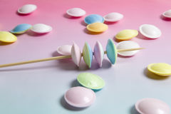 Flying saucer multi coloured candy. Sweets on a gradient background pink and blue Stock Photo