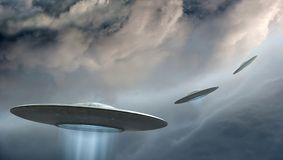 Flying saucers. 3d render of flying saucers ufo on dramatic clouds background royalty free illustration