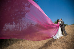 With flying shawl. Bride and groom with the pink shawl Stock Photo