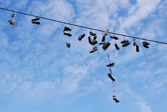 Flying shoes. Old shoes hanging from a cable Stock Photo