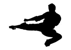 Flying Side Kick. Silhouetted Male Figure doing a flying karate kick Royalty Free Stock Image