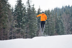 Flying skier at jump from the slope of mountains. In orange jacket, he performing a high jump and looking apprehensive about the landing with forest in Stock Images