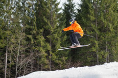 Flying skier man at jump from the slope of mountains. Skier male flying at jump from the slope of mountains in orange jacket performing a high jump and looking Stock Images