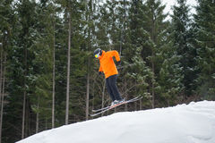 Flying skier man at jump from the slope of mountains. In orange jacket performing jump with forest in background. Side view Royalty Free Stock Photo