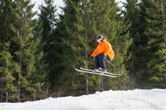 Flying skier man at jump from the slope of mountains. In orange jacket performing a high jump with forest in background. Side view. Bukovel, Ukraine stock photos