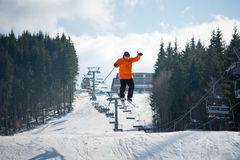 Flying skier man at jump from the slope of mountains. Flying skier at jump from the slope of mountains in orange jacket performing a high jump, with forest and stock photo