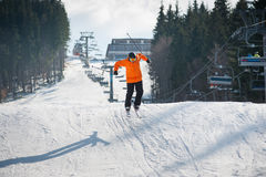 Flying skier man at jump from the slope of mountains. Flying skier at jump from the slope of mountains in orange jacket performing a high jump, with forest and royalty free stock photography
