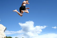Flying Into The Sky. A young man jumps from a cliff into the sea Stock Images