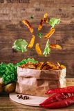 Flying slices of baked potato on wooden background. Lettuce, paprika, parsley. Fastfood. Stock Photography