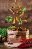 Flying slices of baked potato on wooden background. Lettuce, paprika, parsley. Fastfood. With spices. Stock Photos