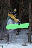 Flying Snowboarder. In mountain forest Stock Photos