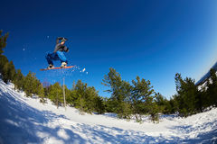 Flying snowboarder in the mountains. On the background of blue sky Stock Photography