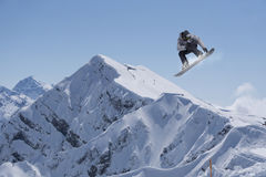 Flying snowboarder on mountains Royalty Free Stock Photo
