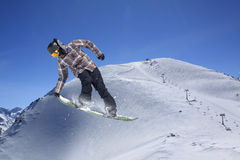 Flying snowboarder on mountains. Extreme sport Royalty Free Stock Photos
