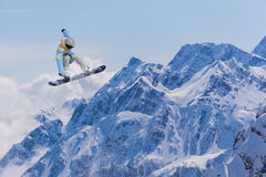 Flying snowboarder on mountains. Extreme sport Royalty Free Stock Images