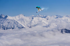 Flying snowboarder on mountains Stock Photos