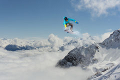 Flying snowboarder on mountains Stock Image