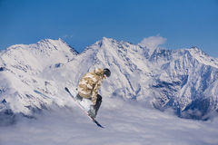 Flying snowboarder on mountains, extreme sport. Flying snowboarder on mountains, extreme winter sport Stock Photos