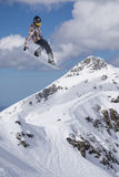 Flying snowboarder on mountains, extreme sport. Flying snowboarder on mountains, extreme winter sport Royalty Free Stock Image