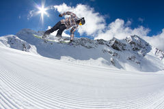 Flying snowboarder on mountains, extreme sport. Flying snowboarder on mountains, extreme winter sport Royalty Free Stock Images