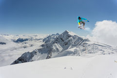 Flying snowboarder on mountains, extreme sport. Flying snowboarder on mountains, extreme winter sport Stock Photography