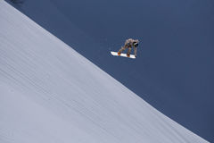 Flying snowboarder on mountains. Extreme sport. Royalty Free Stock Images
