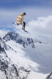Flying snowboarder on mountains. Extreme sport. Royalty Free Stock Photography