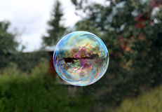 Flying soap bubble reflecting village house Stock Photo