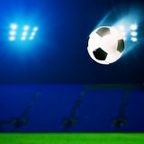 Flying soccer ball over green field Royalty Free Stock Photos