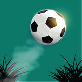 Flying soccer ball. With silhouette grass background Royalty Free Stock Image