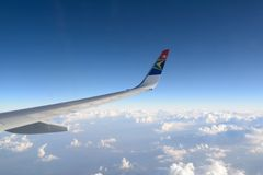 Flying with South African Airways. Looking out the window of a South African Airways aircraft with a wing in the foreground and clouds below Royalty Free Stock Photography