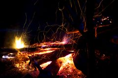 Flying sparks and the flame of a night fire Royalty Free Stock Photography