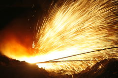 Flying sparks. Sparks flying when lancing the tap-hole of a submerged arc furnace, with heaps of casting sand to the front, at a South African producer of charge Stock Image