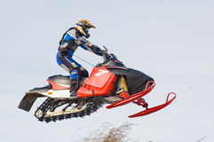 Flying sportsman on snowmobile stock images