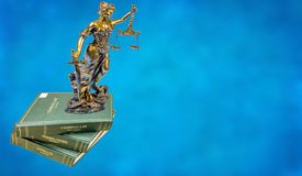 Flying statue of justice and legal books stock images