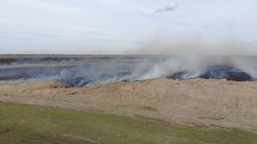 Flying straight ahead over burning field. Fire and smoke, black charred land. Emergency stock video