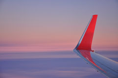 Flying at sunrise, red airplane wing and winglet Royalty Free Stock Photo