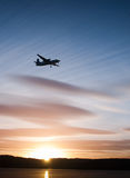 Flying sunset. Airplane flying in the sunset over the water Stock Image