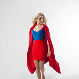 Flying super girl, heroine. Young and beautiful blonde in image of superheroine in red Cape growing Royalty Free Stock Images