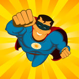 Flying Superhero. Illustration of a happy awesome powerful comic superhero with red and blue disguise flying with explosion of sunbeams behind Royalty Free Stock Photo