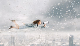 Flying superwoman. Young pretty businesswoman flying in blue sky sreaming in megaphone Stock Photo