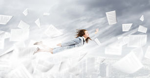 Flying superwoman. Young pretty businesswoman flying in sky above city Stock Photos
