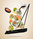 Flying sushi pieces served on plate, separated on colored background. Many kinds of popular sushi food with chopsticks. Concept of flying asian dish with stock photos