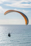 Flying tandem paraglider over the sea, vertical shot Royalty Free Stock Image