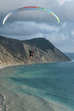 Flying tandem paragliders over the sea close to mountains, vertical view of the landscape Stock Images