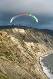 Flying tandem paragliders over the sea close to mountains, vertical view of the landscape Stock Image